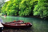 stock photo of dock a lake  - Boats docked in the tranquil waters of Plitvice Lakes National Park Croatia