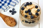 picture of masonic  - Blueberry and banana breakfast overnight oatmeal in a mason jar with spoon on white wood - JPG