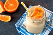 foto of masonic  - Orange fruit smoothie in a mason jar glass resting on checked cloth with fresh orange slices over a slate background - JPG