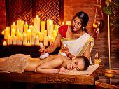 stock photo of panchakarma  - White woman having ayurvedic massage with pouch of rice - JPG
