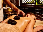 stock photo of ayurveda  - Young woman having Ayurveda black hot stone massage - JPG