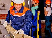 stock photo of millwright  - Old man in blue  builder with circular saw - JPG