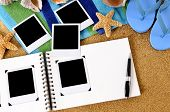 image of  photo  - Photo album on a sandy beach with blank photo prints beach towel starfish and flip flops - JPG