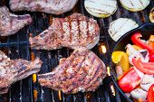 image of pork chop  - Pork chops sizzling over the flames of a summer grill - JPG
