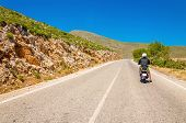 stock photo of vespa  - Young man driving scooter on empty asphalt road - JPG