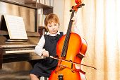 stock photo of cello  - Beautiful small girl in school uniform playing on the cello near the piano indoors - JPG