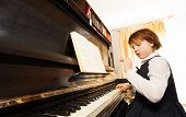 foto of concentration  - Concentrated beautiful small girl in school uniform playing the piano with notes during lesson indoors - JPG