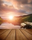 stock photo of jetties  - Sunrise over lake with boats moored at jetty with wooden planks floor - JPG