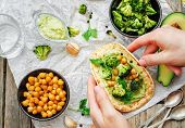 foto of chickpea  - man holding tortilla with roasted broccoli and chickpeas and avocado sauce - JPG