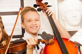 picture of violin  - Smiling girl holding violoncello with other girl near holding violin inside musical school - JPG