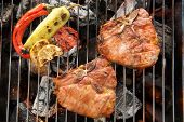 pic of pork chop  - Pork chop steak and vegetable on a flaming BBQ grill - JPG