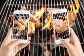 picture of grilled sausage  - friends using smartphones to take photos of sausage and pork chop on the flaming grill - JPG