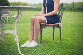 foto of lawn chair  - A young woman is sitting and relaxing on a chair on a lawn in a garden - JPG