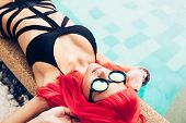 picture of wig  - Fashion photo of sexy young woman with red wig hair in black bikini and sunglasses relaxing beside a swimming pool - JPG