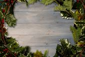 stock photo of holly  - Holly twigs over wooden planks with copy space - JPG