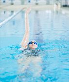 image of goggles  - Young woman in goggles and cap swimming back crawl stroke style in the blue water indoor race pool - JPG