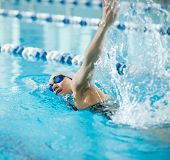 picture of goggles  - Young woman in goggles and cap swimming front crawl stroke style in the blue water indoor race pool - JPG