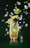 foto of mojito  - Fresh mojito drink with ice cubes and splashes on black background - JPG