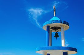 foto of blue-bell  - Typical blue white church tower steeple with bell of Greek church against blue sky - JPG