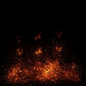 Burning fire with fiery orange flames, sparks and embers exploding into the air on a dark background poster