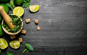 Постер, плакат: Lime Background The Mortar With Mint Sugar Lime Slices And Leaves
