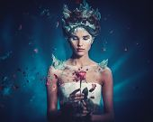 Winter beauty fantasy woman portrait. Beautiful young model girl and blast of frozen rose. poster