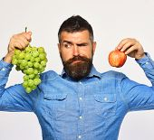 Winegrower With Tricky Face Holds Grapes And Red Fruit. poster