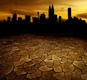 A city looks over a desolate cracked earth landscape in sunset