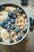 Healthy Breakfast Berry Smoothie Bowl Topped With Banana, Granola, Blueberries And Chia Seeds With C poster
