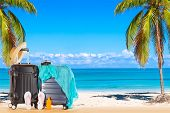 Summer Holidays Concept. Suitcases Baggage With Straw Hat, Blue Pareo, Flip Flops, Sunscreen Lotion  poster