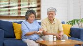 Senior Asian Couple Take Pill Medicine For Elderly Health Care While Sitting On Sofa, Retirement Cou poster