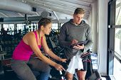 Front view of young Caucasian Male trainer assisting Caucasian female athlete with exercise in fitne poster