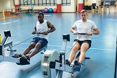 Front view of fit young diverse male athletes exercising with rowing machine in fitness studio. Brig poster