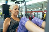 Front view of active senior Caucasian woman exercising with leg press machine in fitness studio. Bri poster