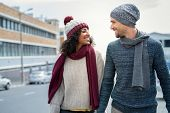 Casual young couple holding hands while walking on the street. Happy couple wearing winter clothes a poster