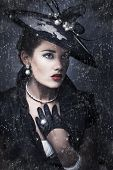 stock photo of olden days  - Dark sombre portrait of a beautiful woman widow dressed in a haute couture black outfit standing outside in the pouring rain during a funeral service - JPG