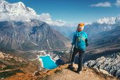 Standing Woman With Backpack On The Mountain Peak. Beautiful Mountains In Clouds, Lake With Azure Wa poster