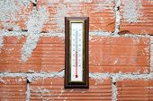Thermometer Hanging On Red Brick Wall