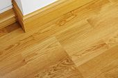 stock photo of up-skirt  - Close up showing some laminate flooring and mdf imitation wood skirting boards in newly constructed house - JPG
