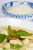stock photo of curry chicken  - Colorful presentation of green curry and a bowl of rice.