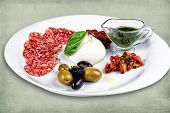 stock photo of charcuterie  - restaurant dish consisting of meats olives egg and sauce - JPG