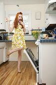 Full length of a terrified young woman looking at open oven