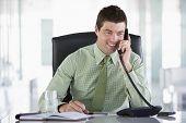 Empresario sentado en la oficina con Personal organizador en el teléfono
