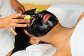 Young Asian Woman in a beauty spa getting a treatment with mask to bleach the skin