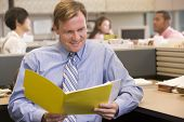 Businessman In Cubicle With Folder Smiling