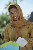 stock photo of dupatta  - Portrait of a happy Indian woman holding shopping bags - JPG