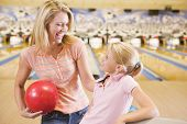 Woman And Young Girl In Bowling Alley Holding Ball And Smiling