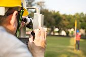 image of theodolite  - Surveyor engineer with partner making measure on the field - JPG