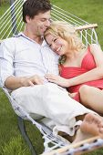 Couples Relaxing In Hammock Smiling