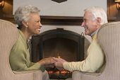 Couples Sitting In Living Room By Fireplace Holding Hands And Smiling